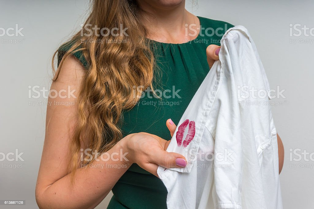 Woman holding a shirt with lipstick of her unfaithful husband stock photo