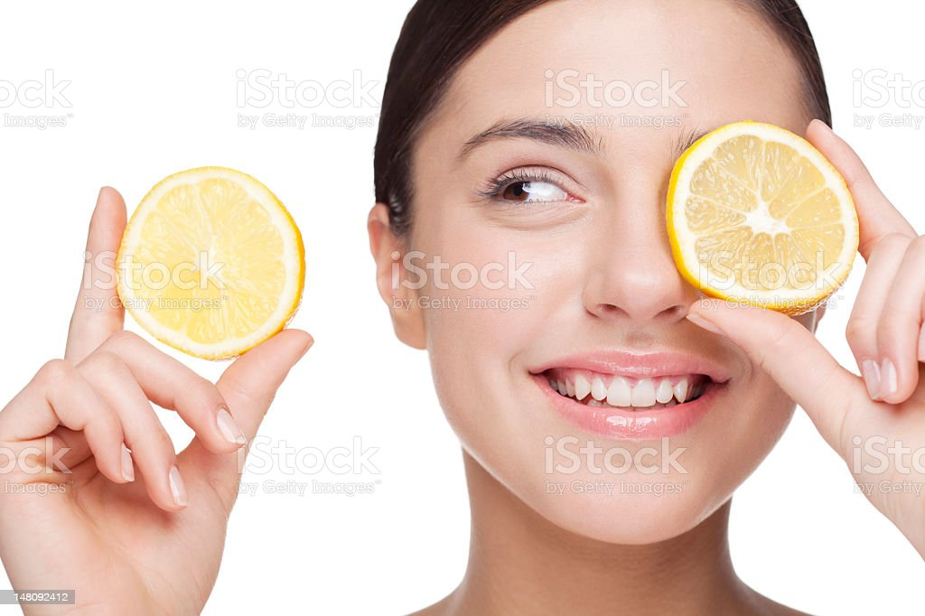 A woman holding a slice of lemon over her eye stock photo