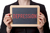 Woman holding a small chalkboard with depression written