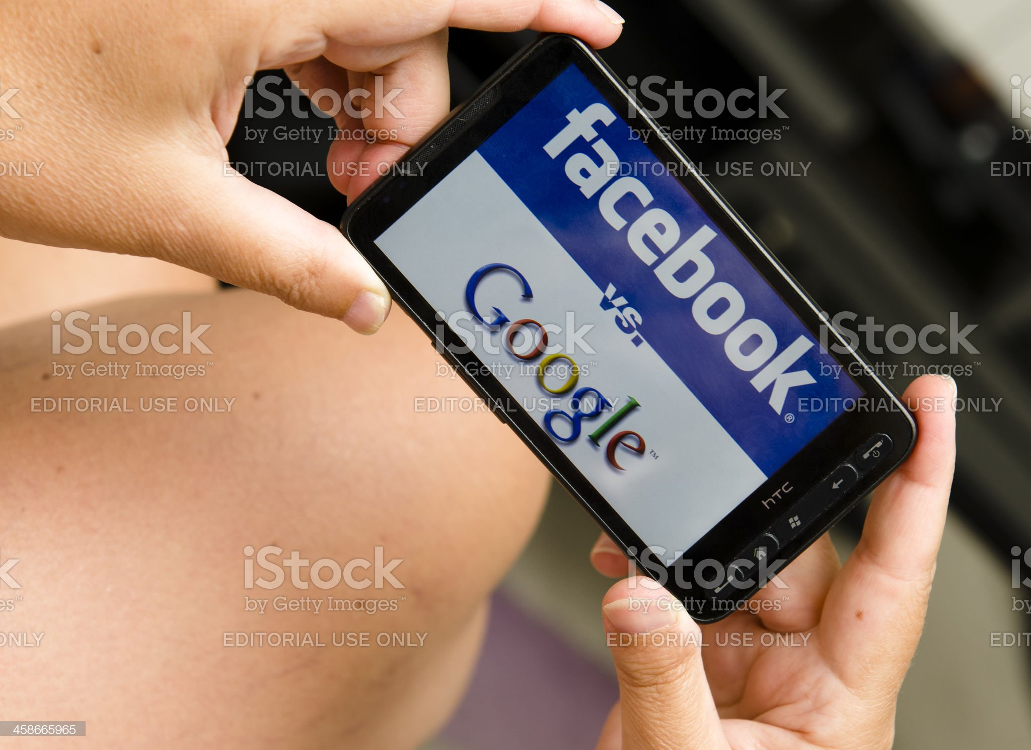 Woman holding a smartphone Google and facebook logo royalty-free stock photo