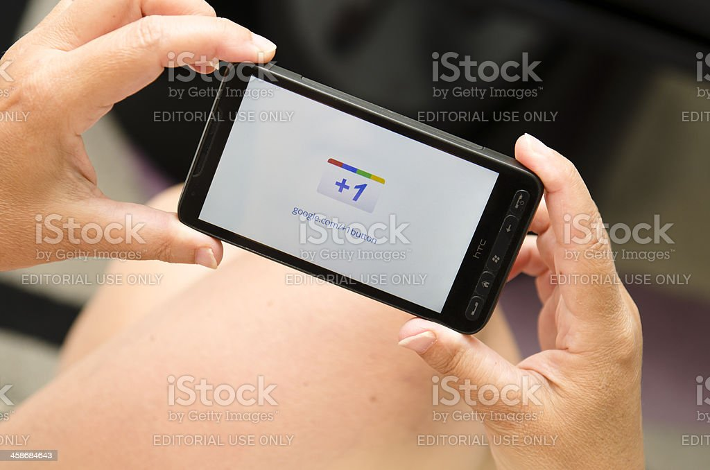 Woman holding a smartphone with Google +1 logo royalty-free stock photo