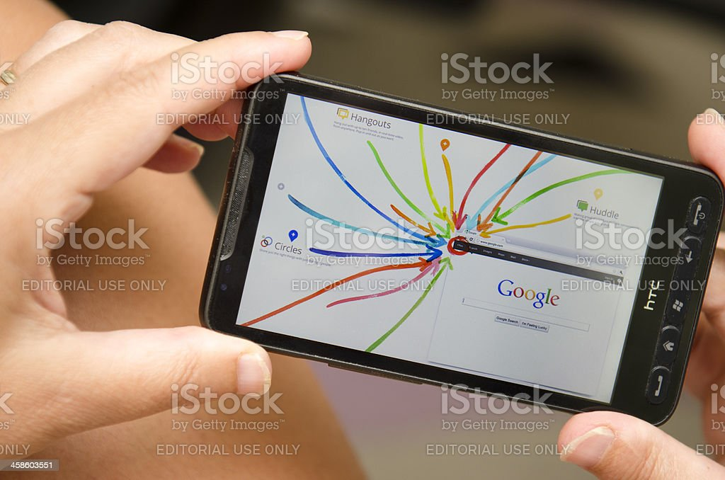 Woman holding a smartphone with Google+ interactive tour stock photo
