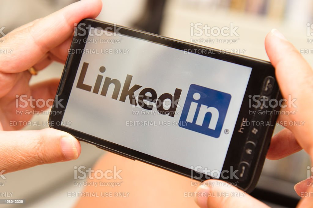 Woman holding a smartphone with linkedin logo stock photo