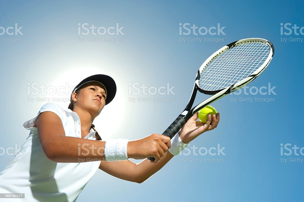Woman holding a tennis racquet ready to serve stock photo