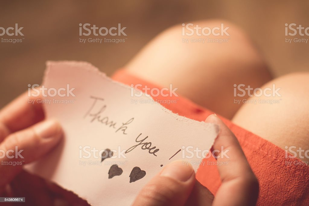Woman holding a thank you note in her hand stock photo