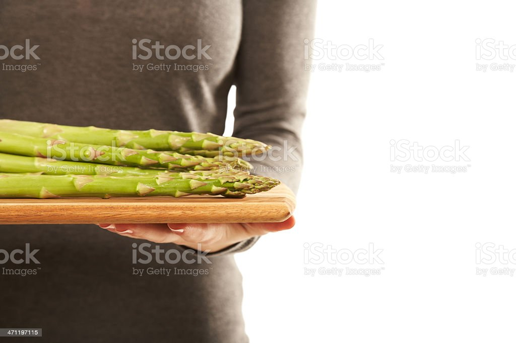 Woman holding a tray full of fresh green asparagus royalty-free stock photo