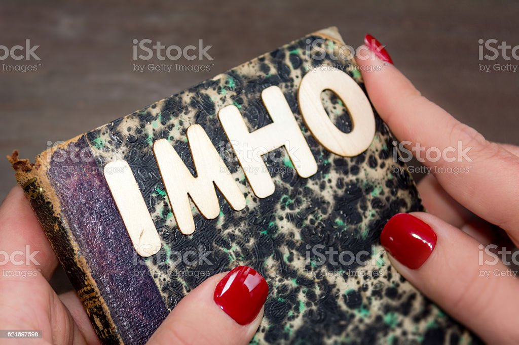 Woman holding a vintage book with the acronym imho stock photo