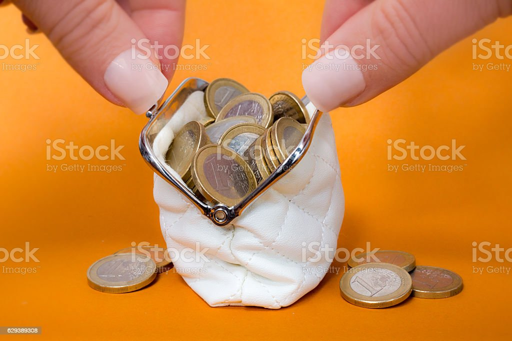 Woman holding a wallet filled   with one euro coins stock photo