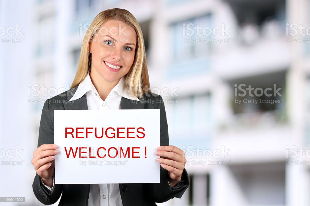 Woman holding a white banner with words ' welcome refugees' stock photo