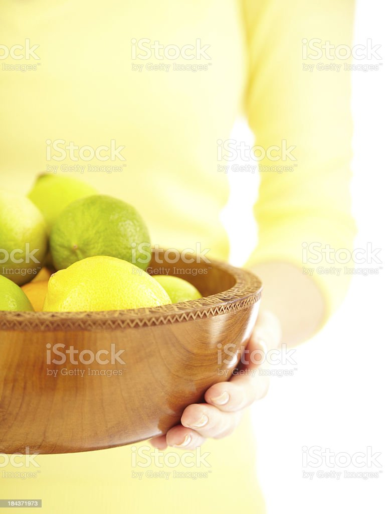 Woman holding a wooden bowl of limes and lemons royalty-free stock photo