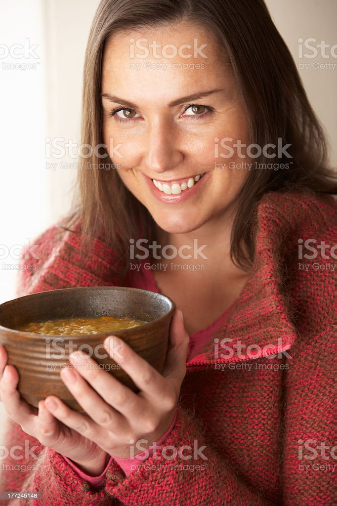 Woman holding a wooden bowl of soup and smiling royalty-free stock photo