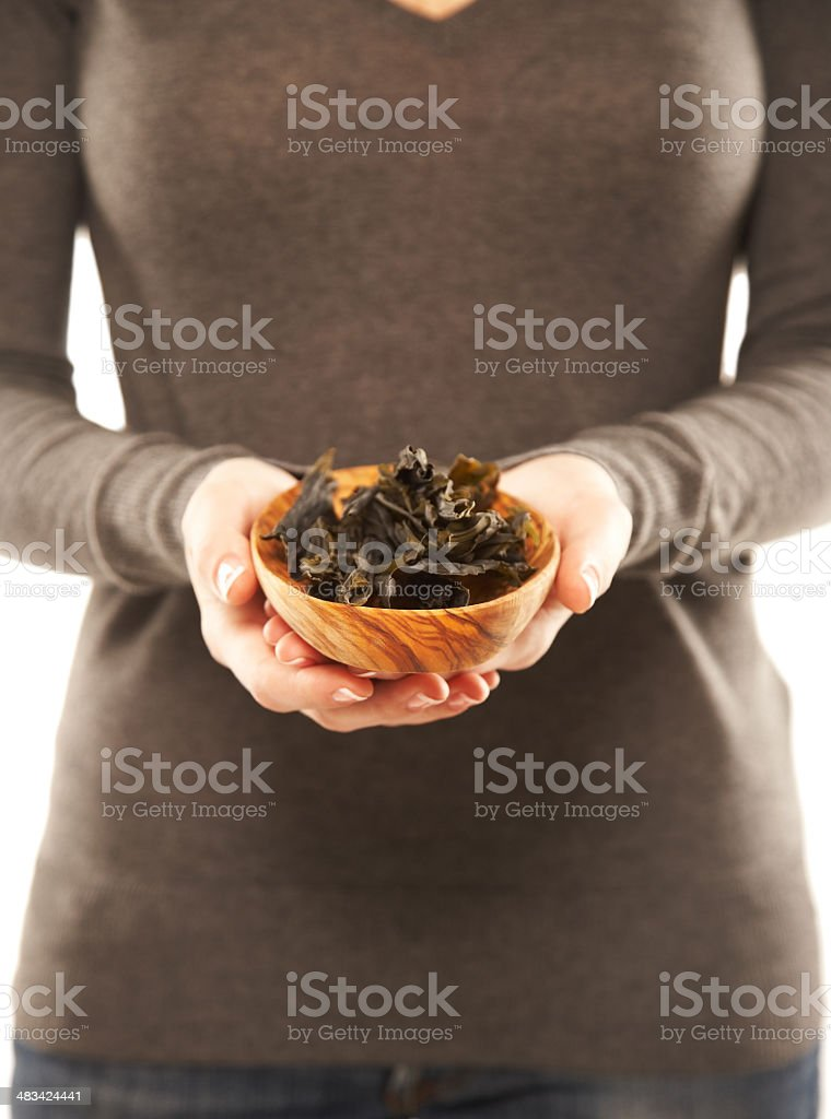 Woman holding a wooden bowl with seaweed stock photo