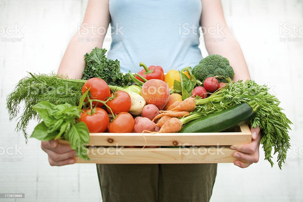 A woman holding a wooden crate filled with vegetables stock photo