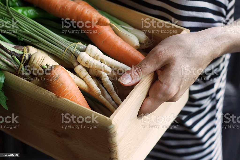 Woman holding a wooden crate of vegetables at the market stock photo