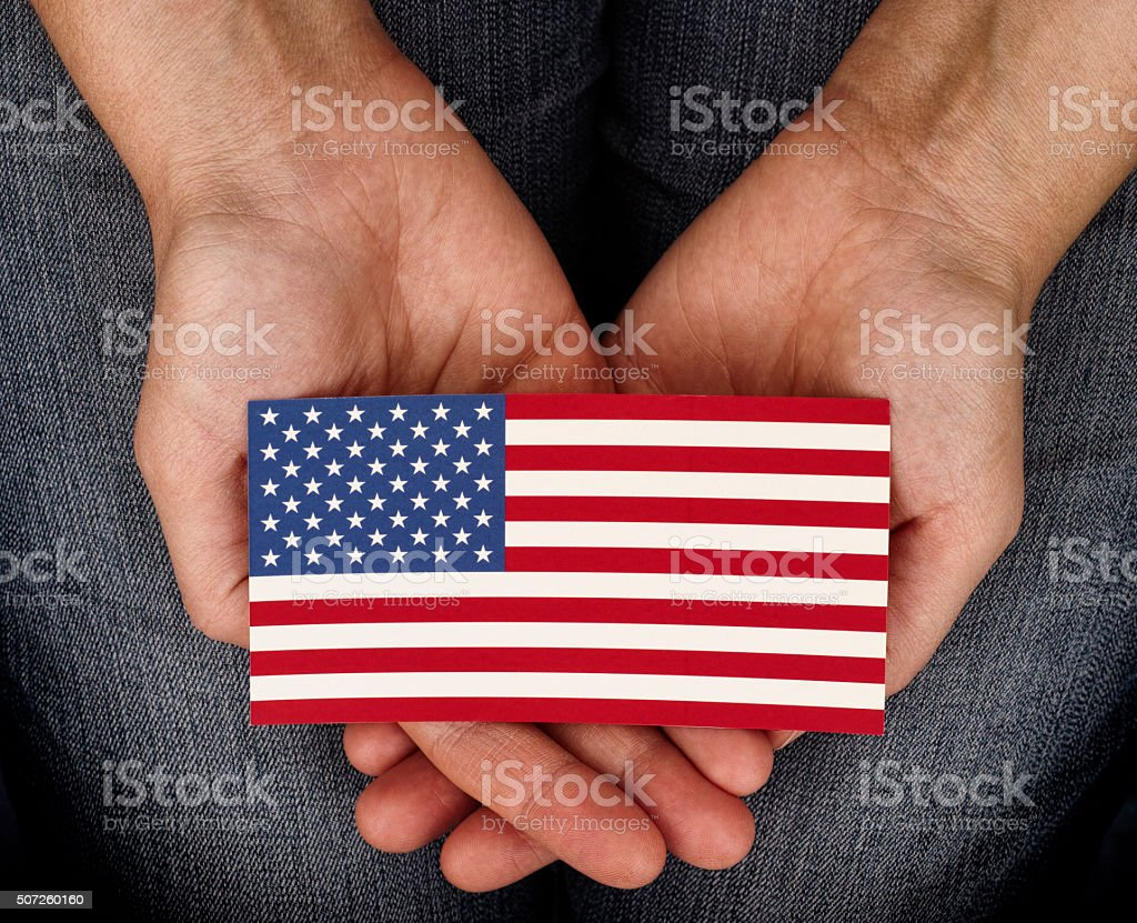 Woman holding American flag on her palms stock photo