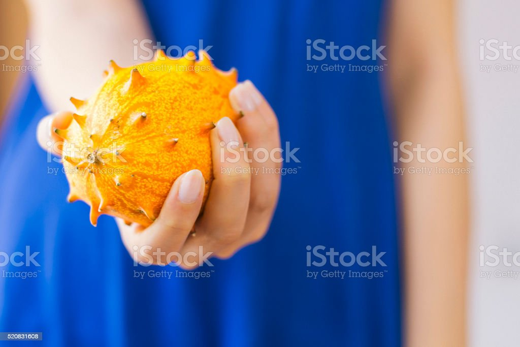 Woman holding an African Horned Melon stock photo