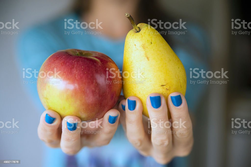 woman holding an apple and a pear stock photo
