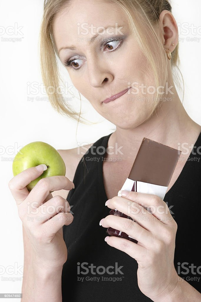 woman holding an apple and chocolate bar royalty-free stock photo