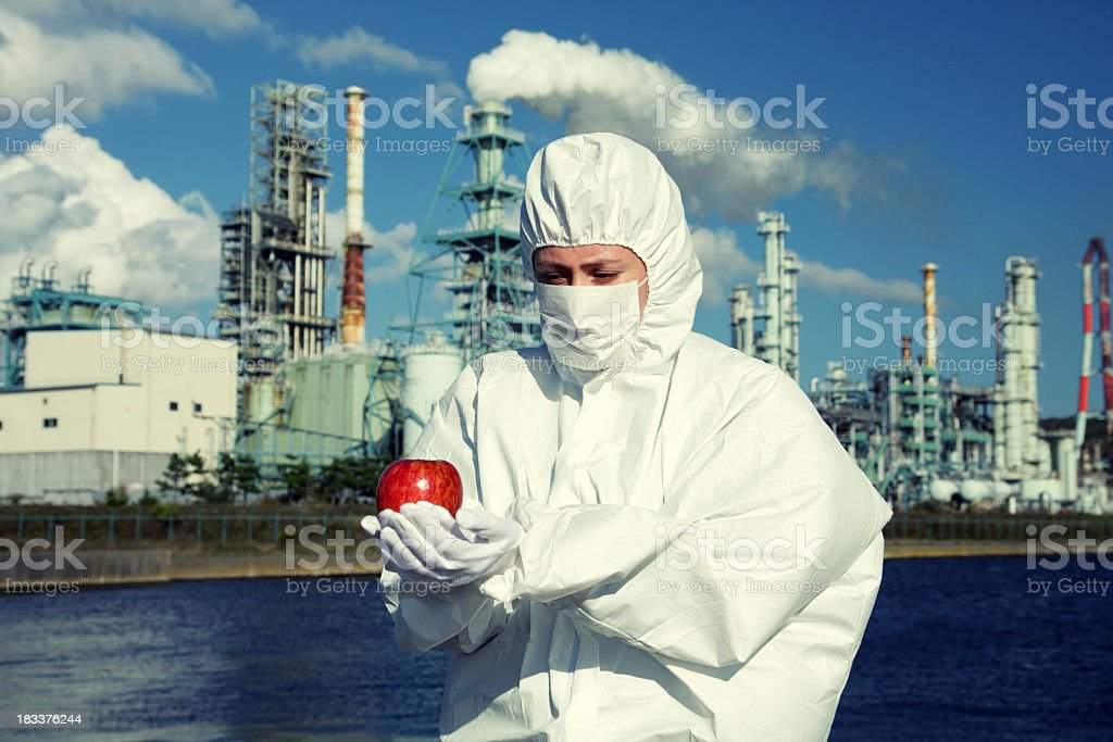Frau hält einen Apfel vor Fabrik Lizenzfreies stock-foto