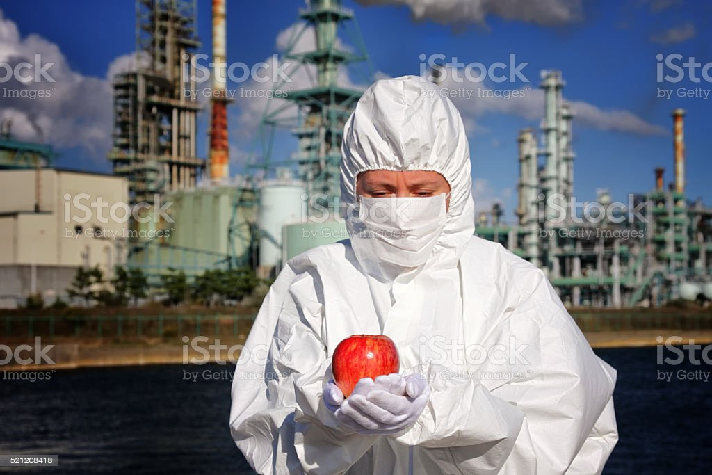 Woman holding an apple in front of factory stock photo