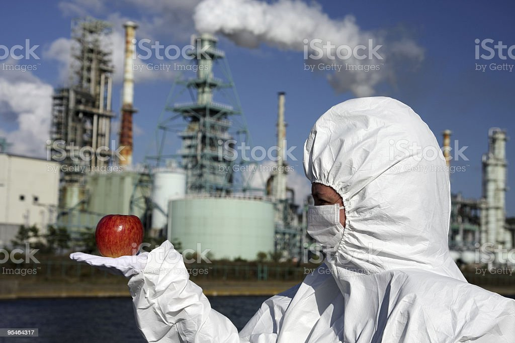 Woman holding an apple in front of factory royalty-free stock photo