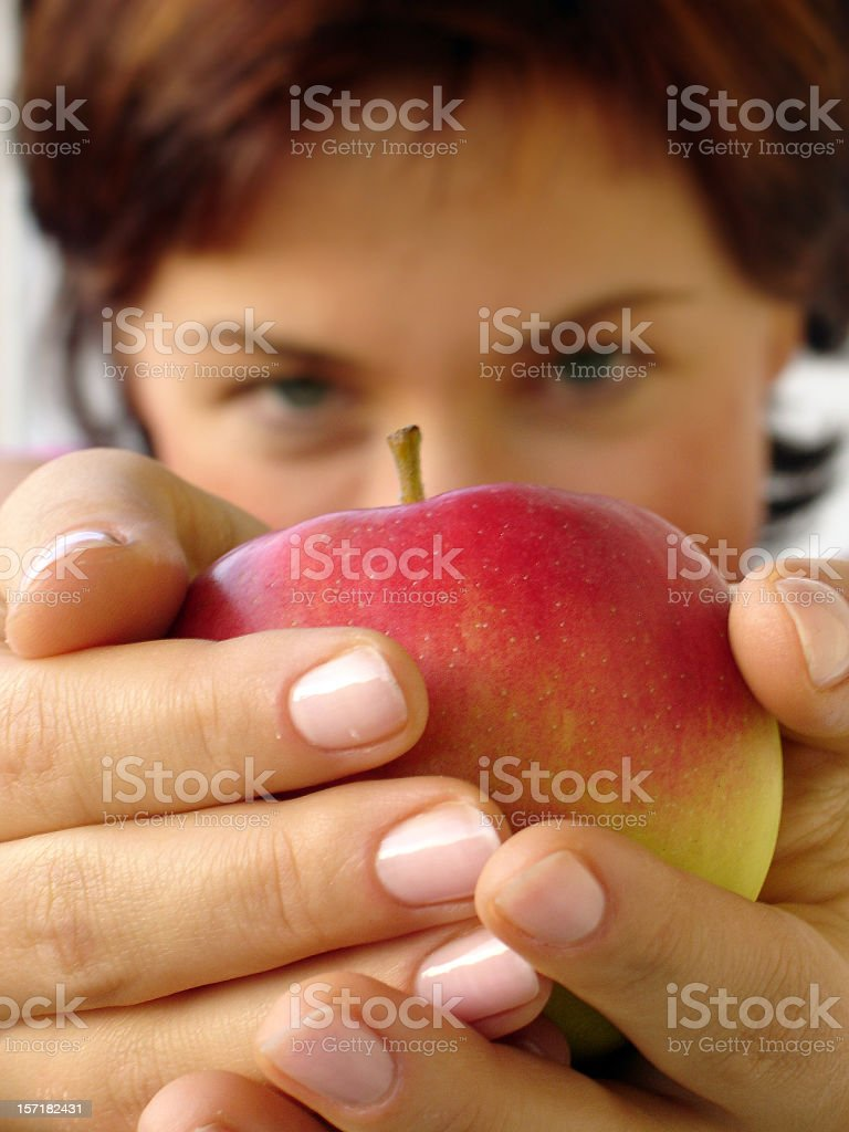 Woman holding an apple in front of her royalty-free stock photo