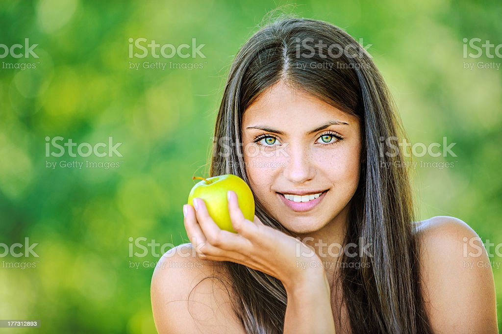 Woman holding an apple in the sun with bare shoulders royalty-free stock photo