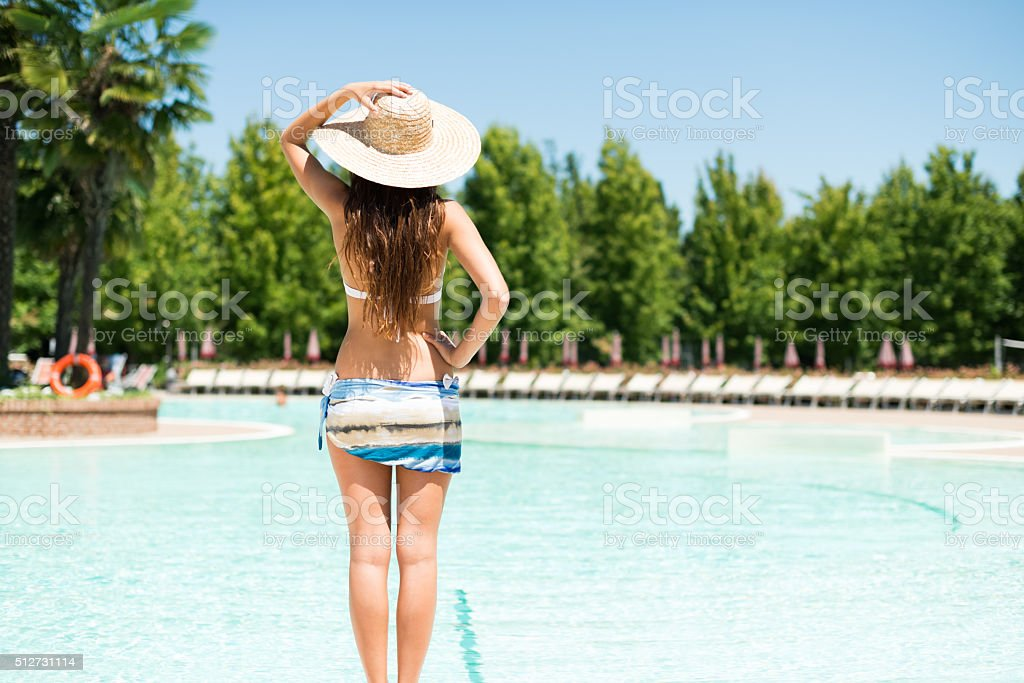 Woman holding an hat in front of a pool stock photo