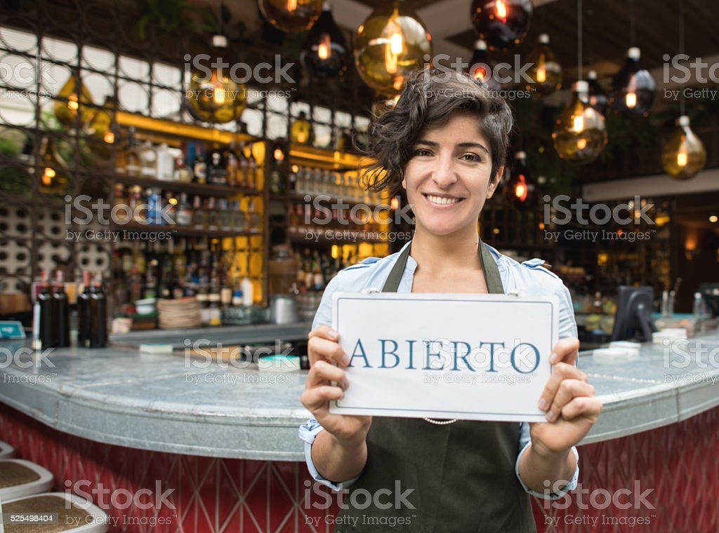 Woman holding an open sign in Spanish at a restaurant stock photo