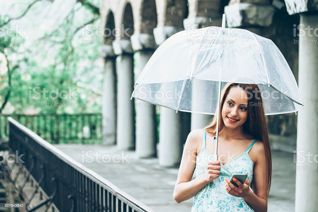 Woman holding an umbrella and using phone under the rain stock photo