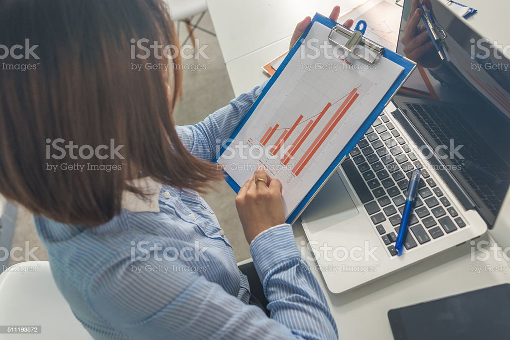 Woman holding and reading document with laptop on table stock photo
