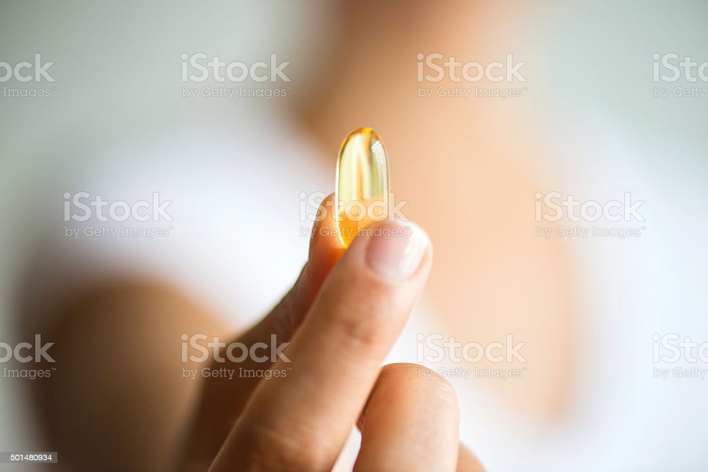 Woman Holding And Showing Omega 3 Capsule stock photo