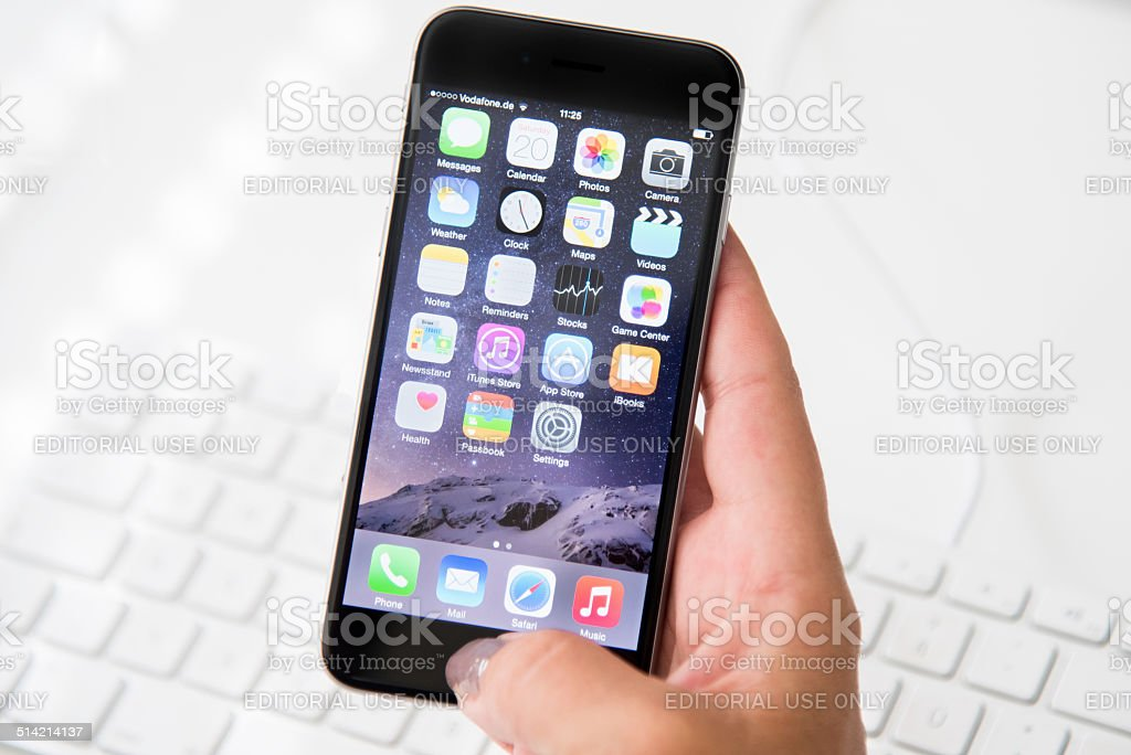Woman holding Apple iPhone 6 stock photo