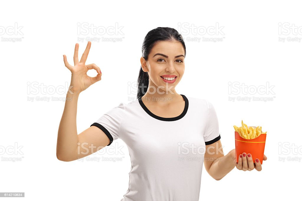 Woman holding bag of fries and making ok gesture stock photo