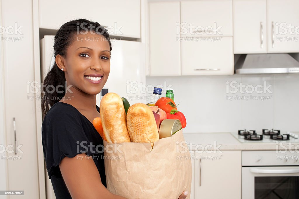 Woman holding bag with grocery products at kitchen. royalty-free stock photo