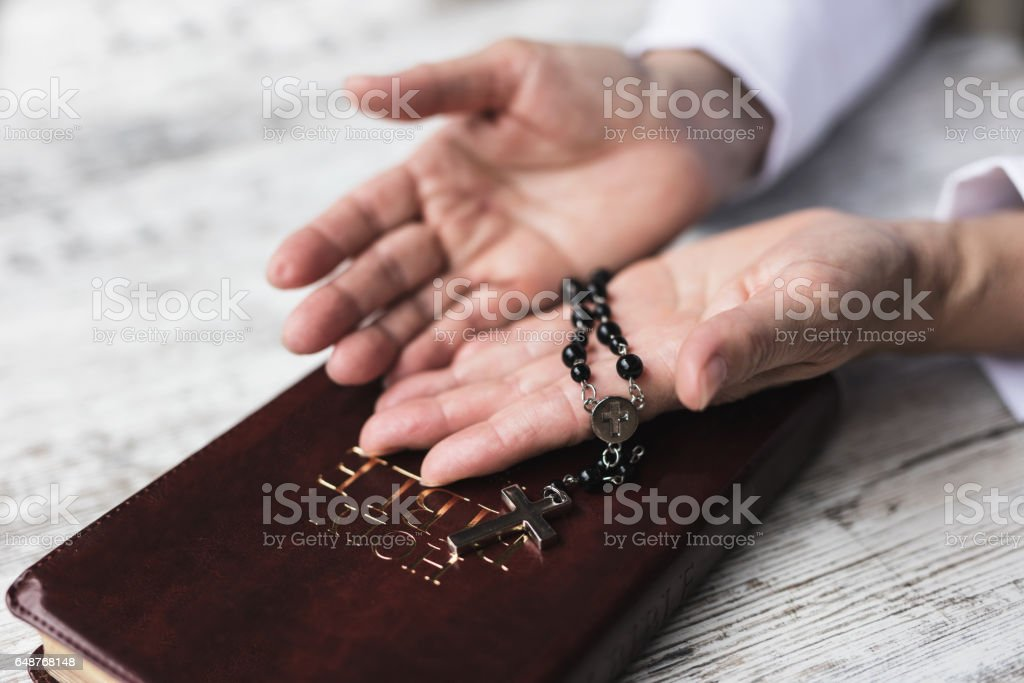 Woman holding balk rosery in her hands over bible stock photo