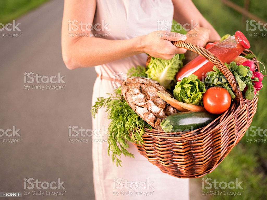 Woman holding basket containing a selection of organic vegetables stock photo