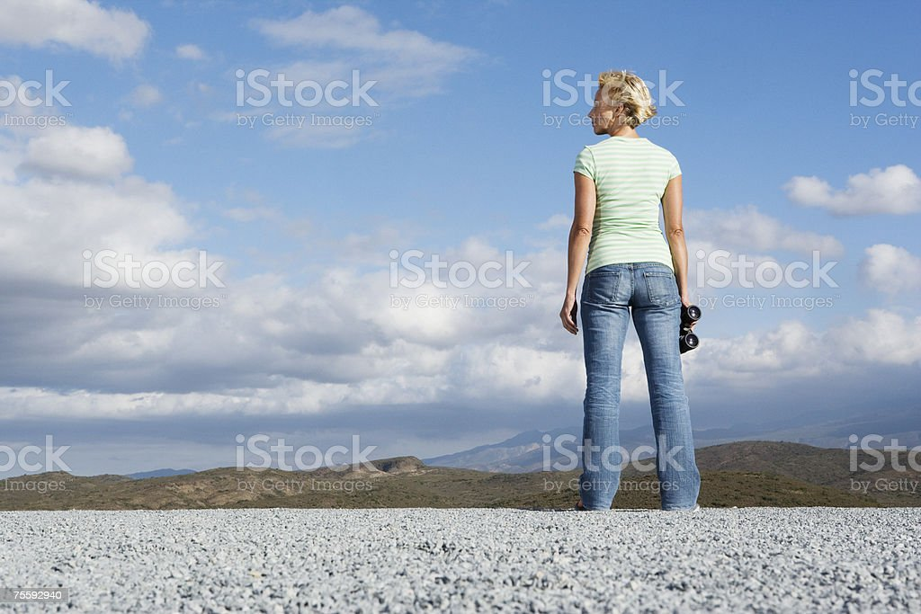 Woman holding binoculars at her side royalty-free stock photo