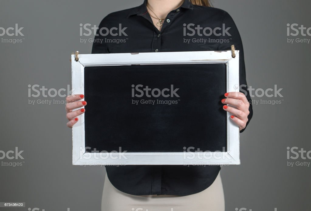 Woman holding blank chalkboard on a dark gray background. Free blank empty copy space for text. Business person or waitress in a restaurant. stock photo