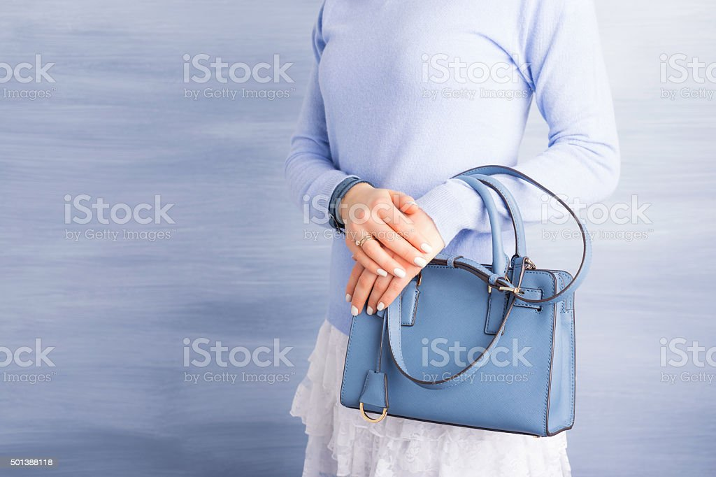 Woman holding blue purse stock photo