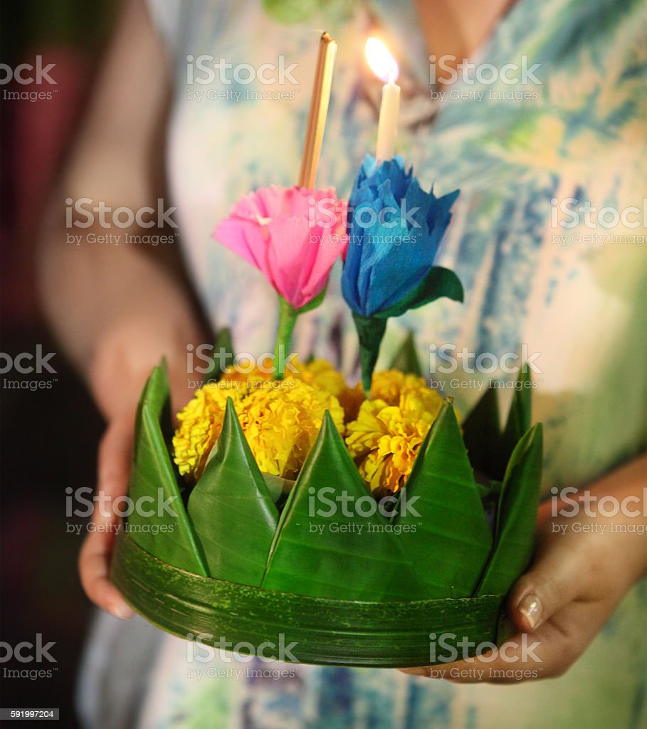 Woman holding boat with candles and flowers Loy Krathong Festival stock photo
