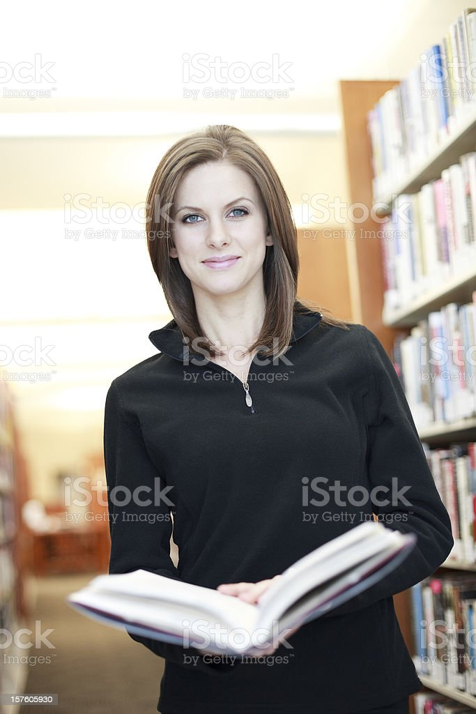 Woman holding book at Library stock photo
