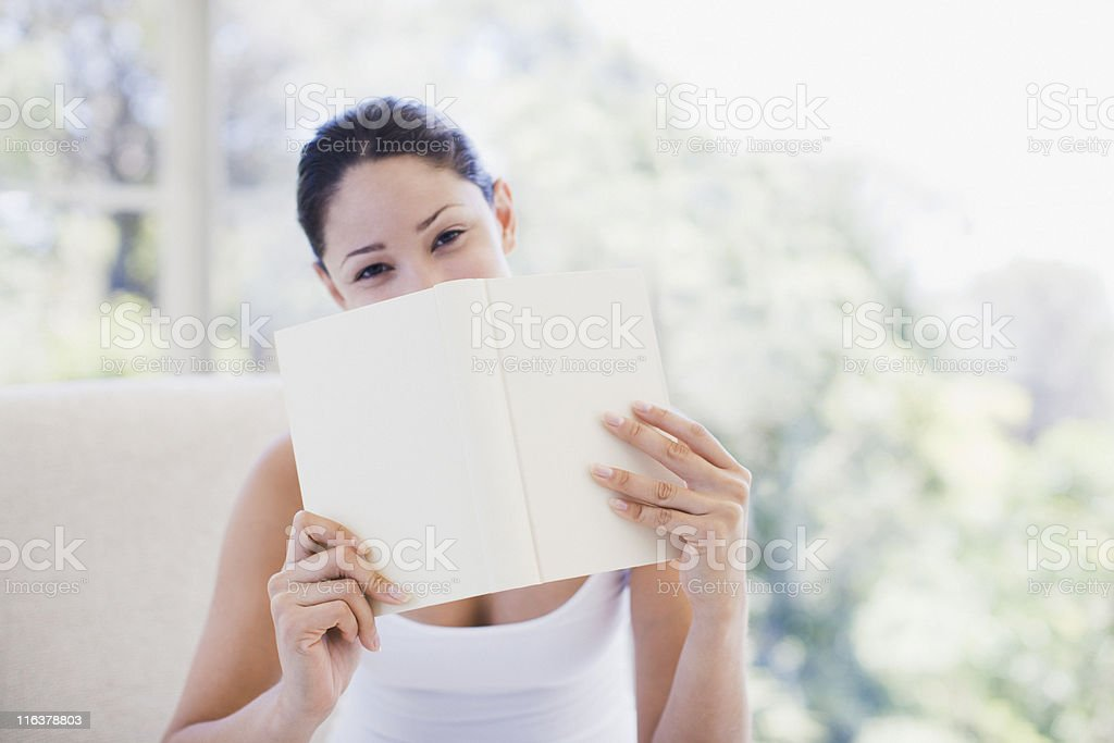 Woman holding book over mouth royalty-free stock photo