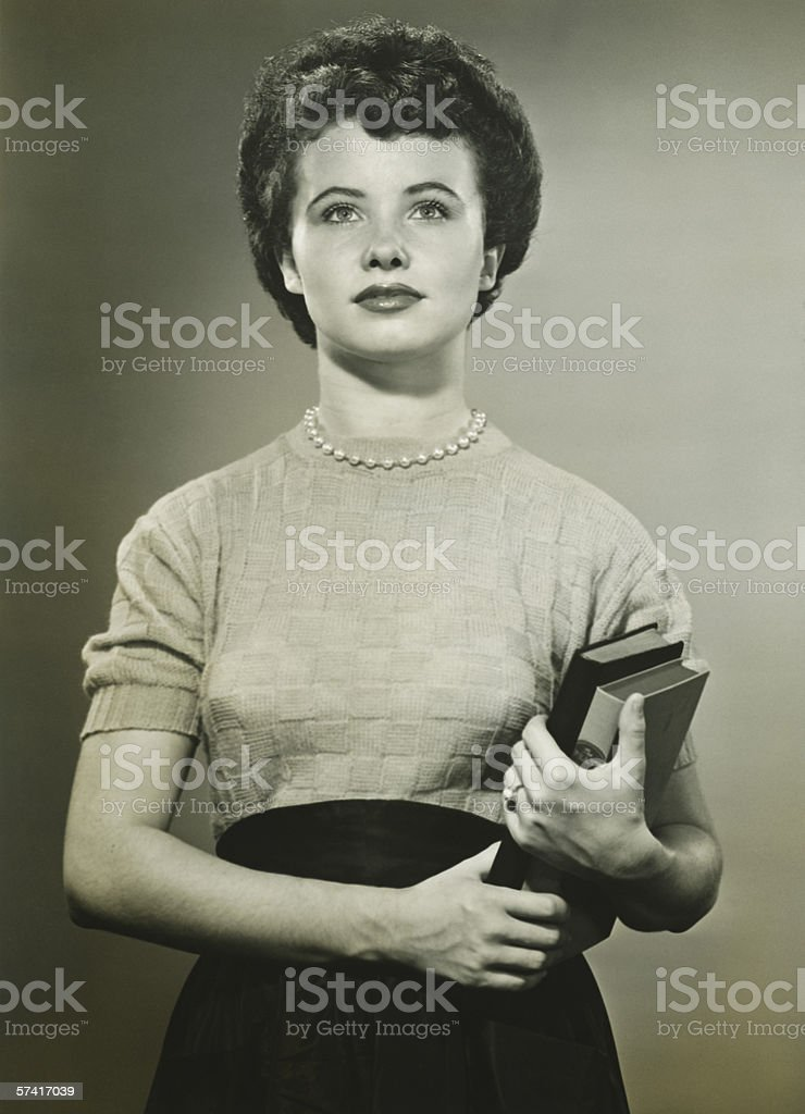 Woman holding books, posing in studio, (Portrait), (B&W) stock photo