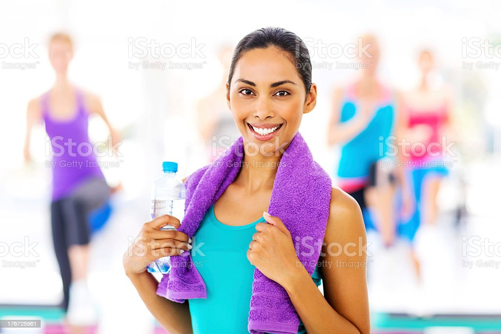 Woman Holding Bottle And Towel With Class In Background royalty-free stock photo