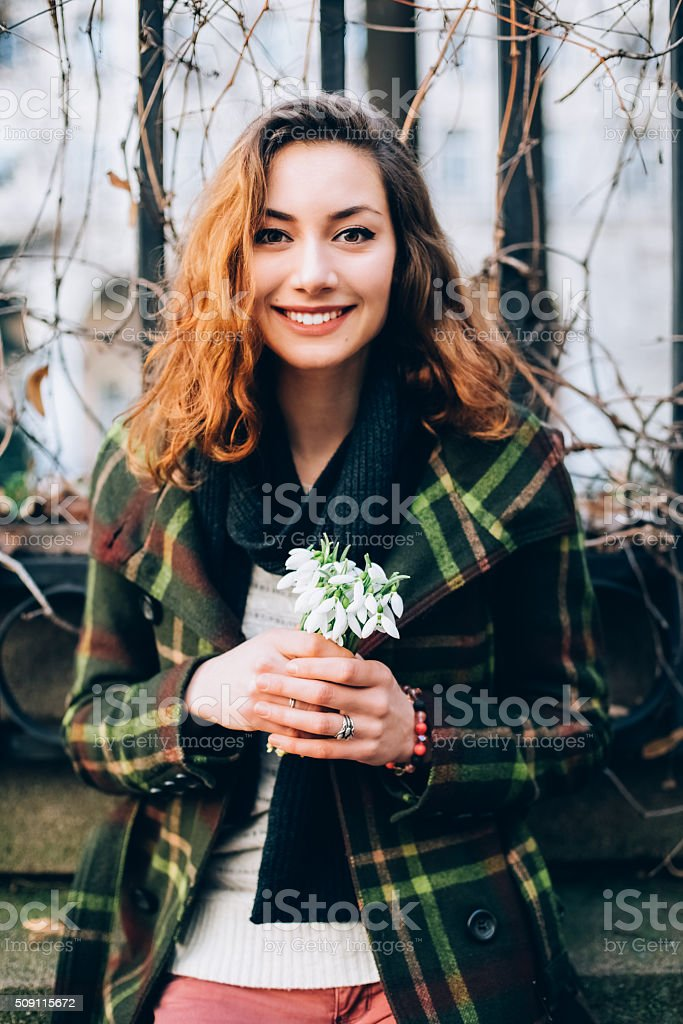 Woman holding bouquet of snowdrops stock photo
