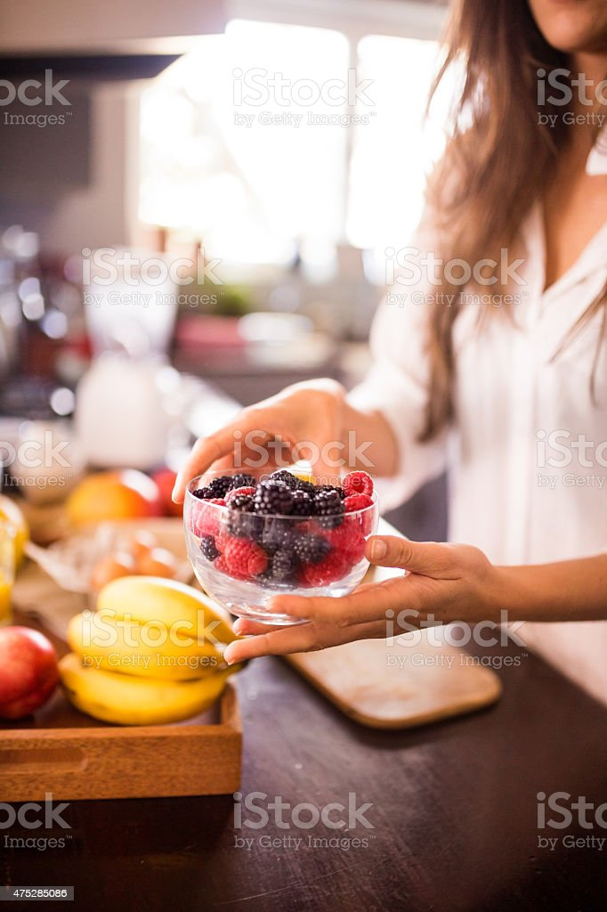 Woman holding bowl of fresh berries for a healthy breakfast stock photo