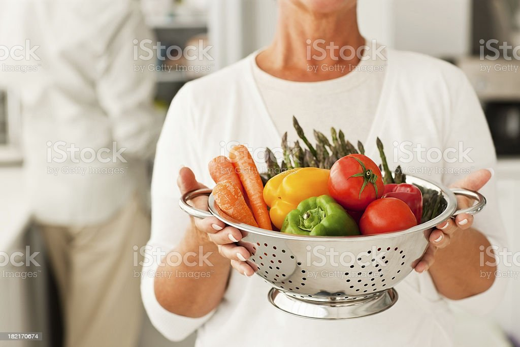 Woman holding bowl of vegetables with husband at the back royalty-free stock photo