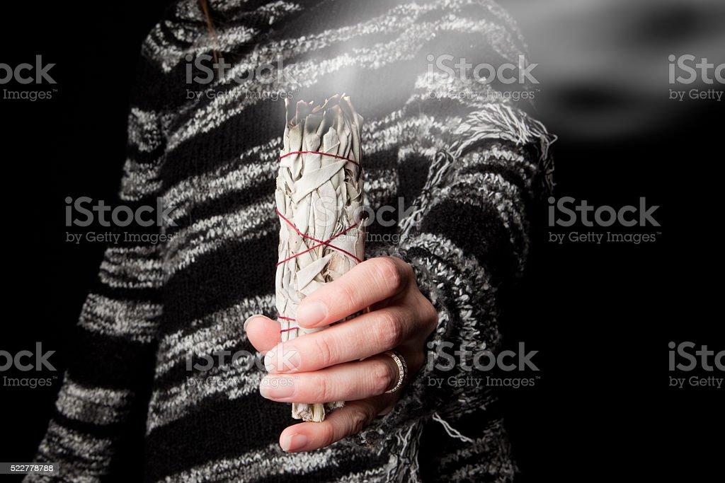 Woman Holding Burning Sage Smudge Stick stock photo