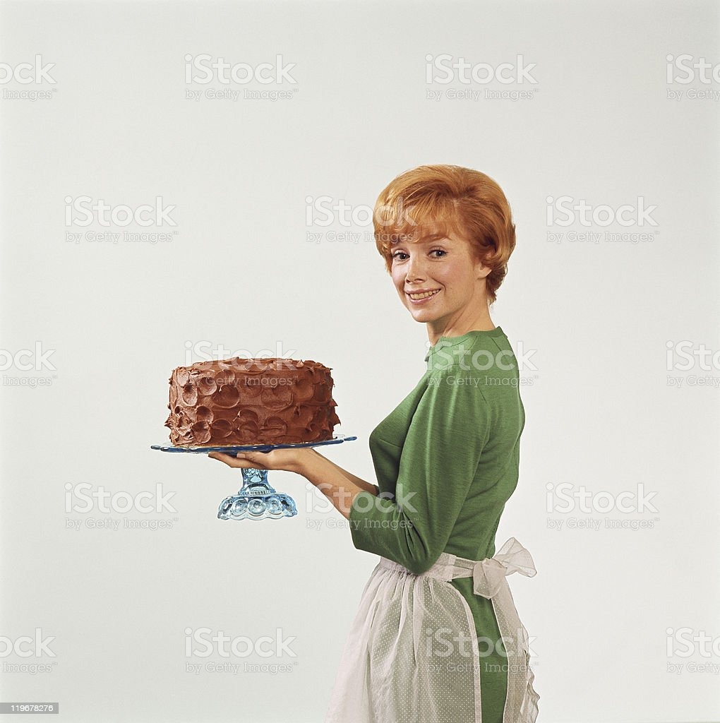 Woman holding cake, smiling, portrait stock photo